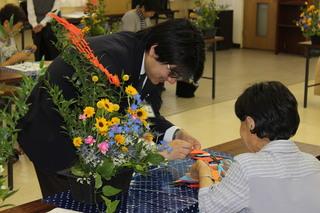 折り紙の飾り作りを行う参加者と指導する大平さん