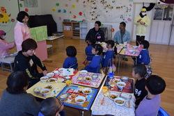 給食の前に献立の説明を聞く園児たち