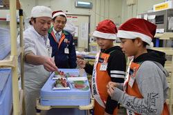鮮魚コーナーで説明を受ける宮島さん(中央)と山上さん(手前)
