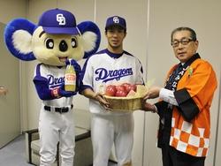 りんごを手渡す小林常務(左)と福田選手とドアラ