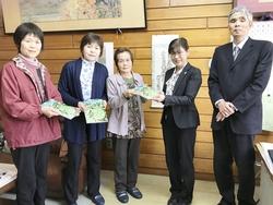 q山下校長(中央右)にちゃぐりんを贈呈する熊谷部長(中央左)ら