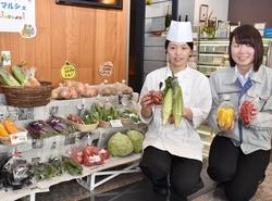 直売コーナーの前でおすすめ野菜を持つ原料理長と神津主任