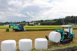 ロールを輩出する細断型ホールクロップ収穫機と運搬する自走式ラップマシーン