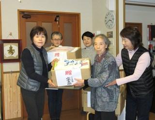 利用者の方にタオルを手渡す金田支部長(左)