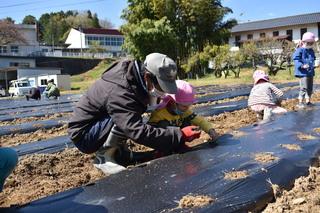 園児と種まきを行う盛年の会メンバー