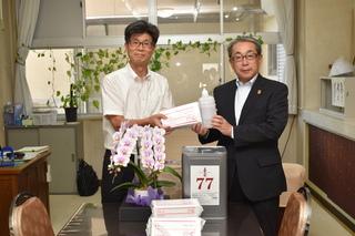 鼎中の斉藤校長㊧へ支給品を贈るJA小林専務㊨