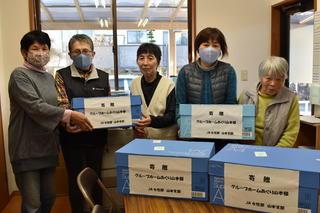 利用者へタオルを手渡すJA女性部山本支部役員(右から2番目:金田支部長)