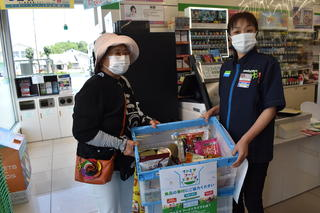 たくさん集まった食材回収ボックスを受け取る「地域を循環させる会」の大澤さん㊧