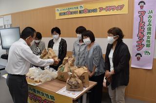 寺沢組合長から米を受け取る女性代表理事