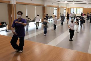 講師の動きに合わせ太極拳を教わる参加者