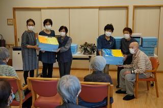 あぐりかなえにて利用者にタオルを手渡す女性部員(左から2番目:松尾 渋谷支部長、左から4番目:鼎 中村支部長)
