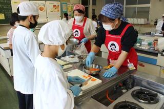 エプロンサポーターに見守られながら調理する児童